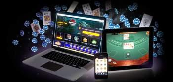 Dator, platta och mobil med casino samt spelmarker och spelkort